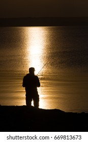 Silhouette of fisherman with fishing rod on the shore of pond at sunrise