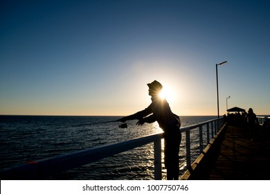 silhouette of fisherman with hat and fish rod standing on sea dock fishing at sunset with beautiful orange sky in vacations relax hobby and leisure holidays concept