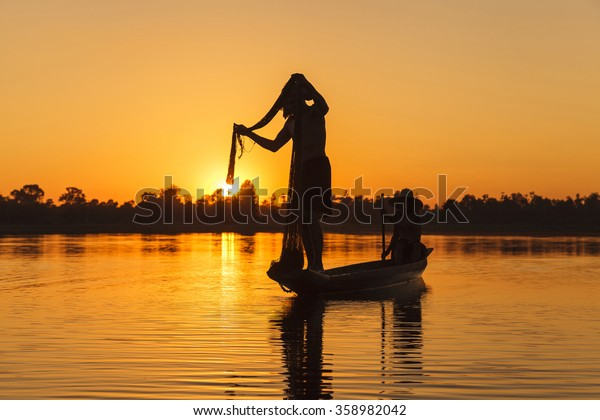 Silhouette of Fisherman with net on the lake at sunset