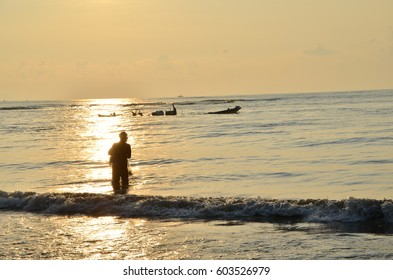 Silhouette of a fisherman netting fish using fishnet during morning sunrise. Visible was sunken boat.
