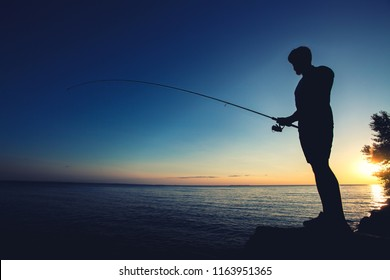 silhouette of a fisherman on the background of the setting sun
