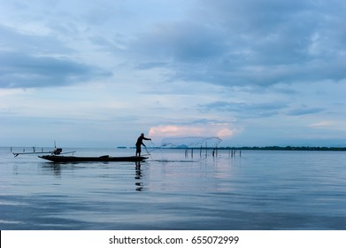 silhouette of fisherman on boat with beautiful sunset sky in  in wetlands Thale Noi, South of THAILAND.
