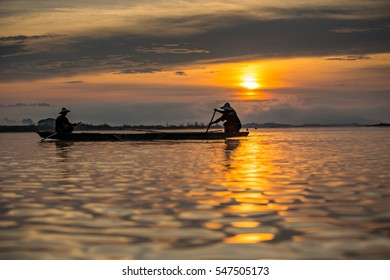 Silhouette fisherman on boat , fishing with nets in the morning.