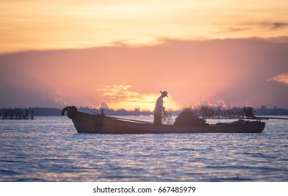 Silhouette fisherman on boat over sunrise background.