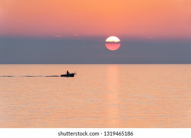 Silhouette of fisherman on small fishing boat with rods at sunset. Fishing at sunrise. Image.