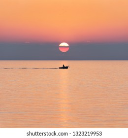 Silhouette of fisherman on small fishing boat with rods at sunset. Fishing at sunrise. Square Image.