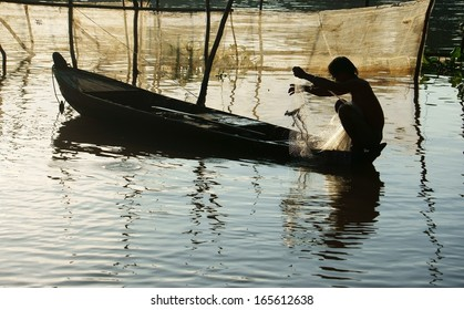 silhouette fisherman sitting on row boat, pick up the net, repair for fishing to catch fish on river at morning in flood season