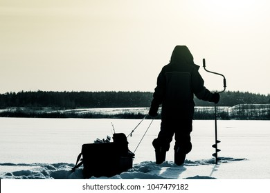 Silhouette of a fisherman with a sleigh. winter fishing. Ice fishing. Leisure. Winter landscape. Fisherman on ice. Life style.