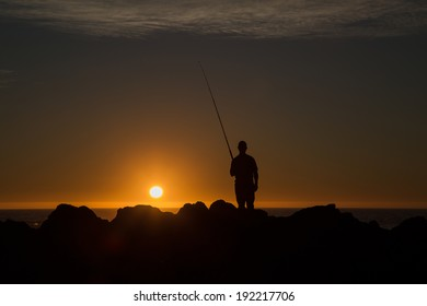 The silhouette of fisherman standing with his fishing rod on the rocks in the sunset, catching fish from the side.
