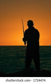 Silhouette of a fisherman as the sun sets on cottesloe beach , Perth