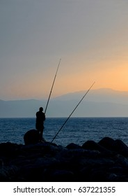 Silhouette of a fisherman at sunrise