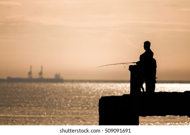silhouette of fisherman at sunrise on the pier