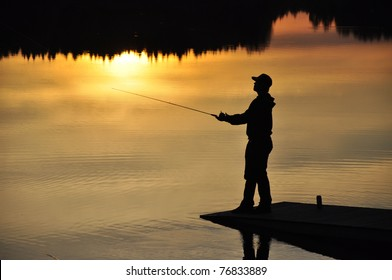 Silhouette of a fisherman at sunset