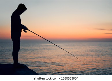 Silhouette of a fisherman at sunset on the background of the sea and sky
