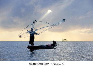 Silhouette of a fisherman throwing his net with beautiful sky.