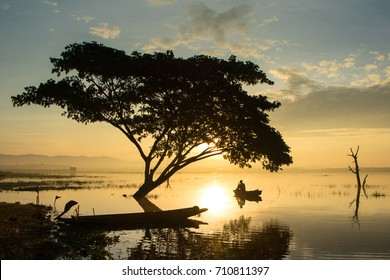The silhouette of the fisherman and the tree in the lake in the background is the sun rising. In the morning.  Beautiful early morning sun, portrait, waves.