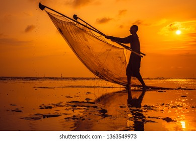 Silhouette of fisherman with vibrant orange sky background