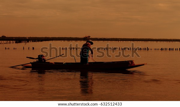 silhouette of fisherman working on a small boat in a mud flat in the morning