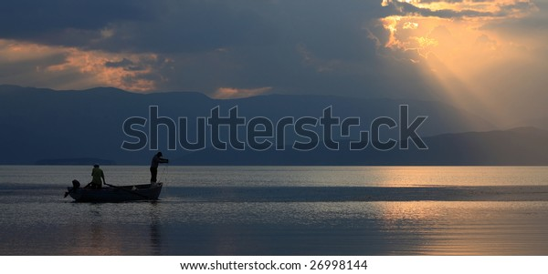 silhouette of a fishermans at sunset