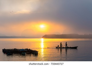 Silhouette of fishermen are fishing nets on a small boat in the morning