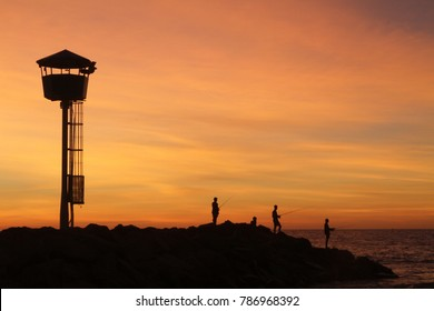 Silhouette of fishermen fishing off the rocks at sunset off City Beach Groyne, Perth, Western Australia