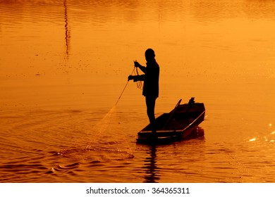 Silhouette fishermen fishing in the pond, Thailand