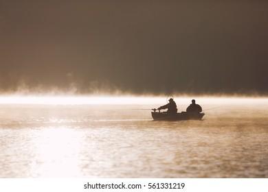 Silhouette of fishermen on lake at dawn