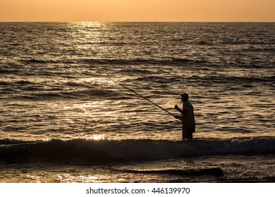 A silhouette of a fishermen standing in the water with his thumbs up at sunset