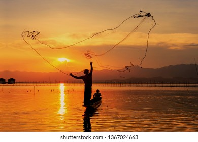 Silhouette of fishermen using coop with beautiful scenery of nature morning sunrise