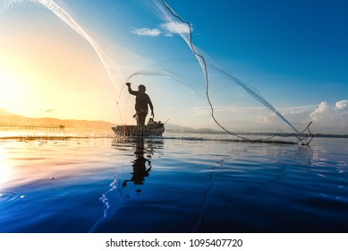 Silhouette of fishermen using coop-like trap catching fish in lake with beautiful scenery of nature morning sunrise. Beautiful scenery at Bang-Pra, Chonburi Province Thailand.