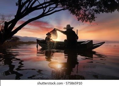 Silhouette of fishermen using coop-like trap catch fish at the Bangpra lake with beautiful scenery of nature during sunrise time. Bang Pra Reservoir at Chonburi province in Thailand
