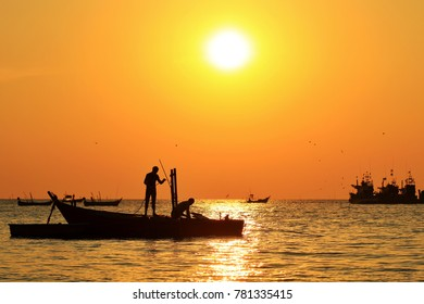 silhouette fishing boat and fisherman in sea at evening in winter.