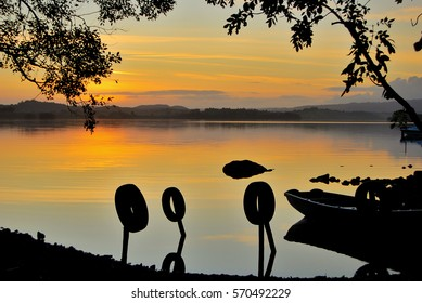Silhouette of a fishing boat on the shore of Lough Erne on a calm morning
