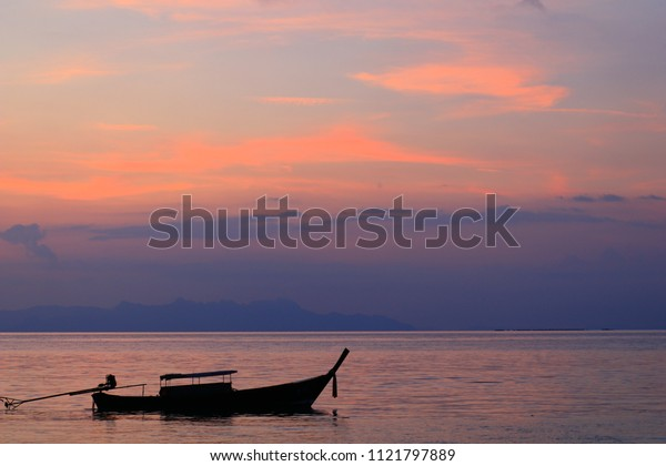 Silhouette fishing boat with smooth sea with purple sky and cloud