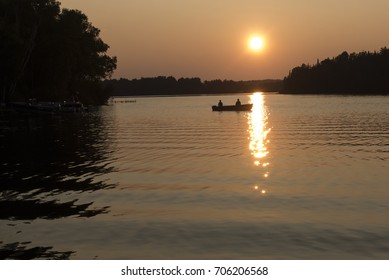 Silhouette of a fishing boat with two people in the bay of a Minnesota lake before sunset, with the sun reflecting off the water.
