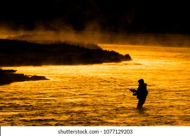 Silhouette of Fishing Flyfishing rod reel in river with golden sunlight