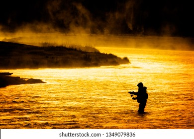 Silhouette of Fishing Flyfishing rod reel in river with golden sunlight early morning fisherman yellowstone river
