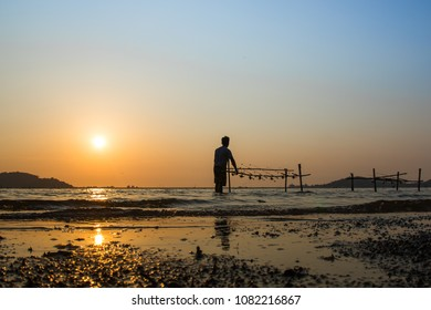 silhouette of a fishing man watching his hook at the seashore. In the evening before sunset. This is a popular holiday activity.
