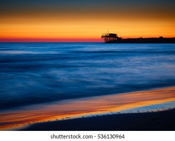 Silhouette of fishing platform known as trabucco at dawn or dusk at sea