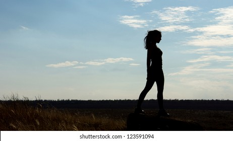 Silhouette of a fit healthy sexy woman standing on the horizon against a late afternoon sky with plenty of copyspace