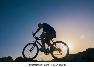 Silhouette of a fit male mountain biker riding his bike uphill on rocky harsh terrain on a sunset.