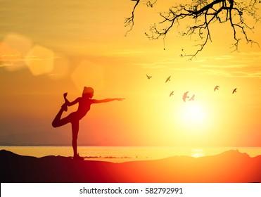 Die Silhouette des Fitness-Athleten, der Yoga praktiziert, vermittelt bei Sonnenuntergang am Strand. Frauen, die sich auf der morgendlichen Meditation auf wunderschönem Himmelshintergrund ausdehnen.Zen Wellness- und Wellness-Konzept.