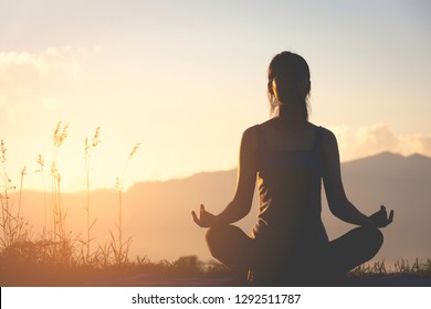 silhouette fitness girl practicing yoga on mountain with sun light