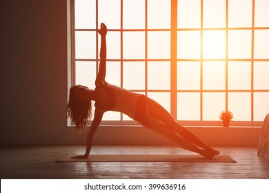 Silhouette fitness woman. Woman silhouette in the window sunset background. Space for text.