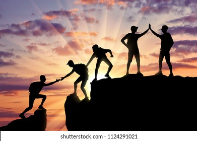 Silhouette of five climbers who climbed to the top of the mountain working in a team. Conceptual scene of alpinists and teamwork