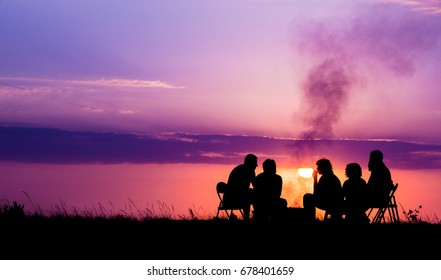 silhouette of five people sitting near campfire against sunset, empty space for text