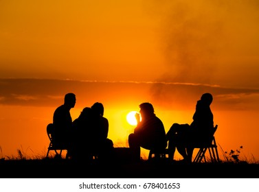 silhouette of five people's group in camping sitting near campfire against sunset