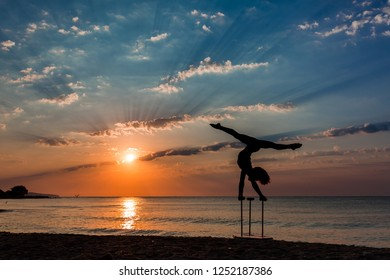 Silhouette Of Flexible Circus Acrobat Female Performer, Practicing On Sand Beach By The Sea At Sunrise. Dramatic Sky With Sparse Clouds.
