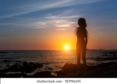 Silhouette of flexible girl with dreadlocks on ocean coast during amazing sunset.