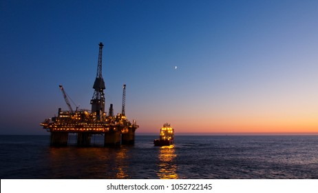 Silhouette of a floating production platform in North Sea region, Norway with sunset as background.
